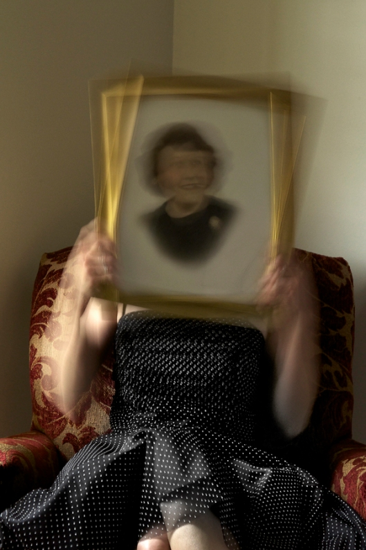 Holding a photo of my grandmother while sitting in her mother's chair.